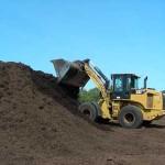 excavator dumping mulch